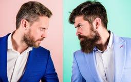 Partnerów biznesowych konkurenci lub biurowi koledzy w kostiumach z spiętymi brodatymi twarzami zamykają up Wrogi lub argumentacy zdjęcia stock
