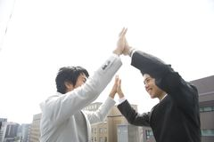Partner. Two young businessmen smiling and giving a double high five outdoor Stock Photography