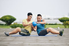 Partner abs workout. Two Vietnamese sportsmen practicing partner abs workout Royalty Free Stock Photos