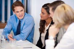 Partner am Arbeitsplatz eine Idee besprechend lizenzfreies stockbild