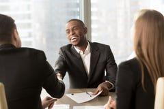 Partner bianco sorridente emozionante di handshake nero dell'uomo d'affari alla m. fotografia stock libera da diritti