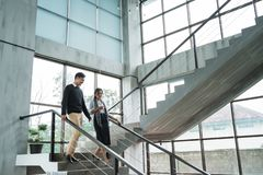 Partner of business walking down with chatting on stairs. In the office building stock photography