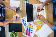 Partner che lavorano allo scrittorio facendo uso del computer portatile e dello smartphone Fotografia Stock Libera da Diritti