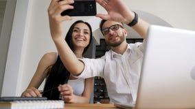Partner che prendono selfie al cellulare nell'area di lavoro archivi video