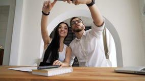 Partner che prendono selfie al cellulare nell'area di lavoro stock footage