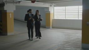 Partner dell'uomo d'affari e della donna di affari che camminano a casa dopo il lavoro che parla mentre tenendo le tazze ed i tel video d archivio