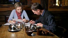 Partner della donna e dell'uomo che firmano contratto in caffè archivi video