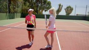 Partner di tennis che discutono le tecniche sulla corte video d archivio