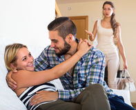 Partner discovering adultery. Unpleasantly surprised girl discovering her boyfriend with another women at home Royalty Free Stock Image
