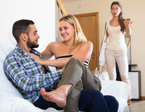 Partner discovering adultery. Unpleasantly surprised girl discovering her young husband with another women at home stock photos
