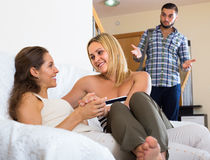 Partner discovering adultery. Unpleasantly surprised guy discovering his girlfriend with another women at home stock image
