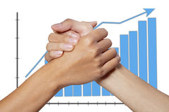 Partner hand on graph background. Partner hand between a businessman and woman on graph background Royalty Free Stock Images