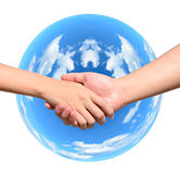 Partner hand between a man and a woman on blue planet. World in signal of protection and conservation Stock Photography