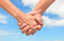 Partner hand between a man and a woman on blue sky background. Partner hand between a men and a women on blue sky background, Teamwork Royalty Free Stock Images