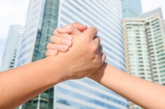 Partner hand between a man and a woman on building background Stock Photos