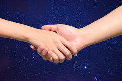 Partner la mano fra l'uomo e la donna su cielo notturno Fotografia Stock