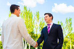 Partner shaking hands. Two happy successful business partner shaking hands outdoor Stock Photography