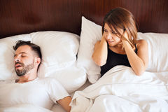 Partner snoring at night. Attractive women covering her ears while her partner snores next to her in bed stock photography