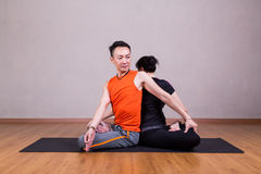 Partner Twist Yoga Pose by a couple. In studio Stock Image
