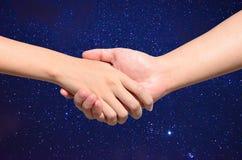 Partnerhand tussen de mens en vrouw op Nachthemel Stock Foto