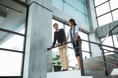 Partners of business chatting about collaboration for next project on the stairs. In the office building stock photo