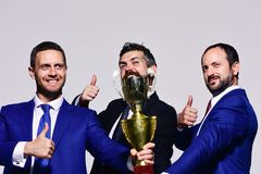 Partners celebrate winning competition. Company leaders hold golden prize. And show thumbs up. Businessmen with happy faces in formal suits on grey background royalty free stock photography