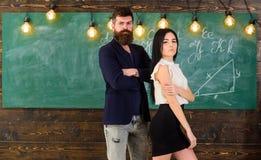 Partners concepto El hombre con la barba y el profesor atractivo de la muchacha se colocan en la sala de clase, pizarra en fondo  Foto de archivo libre de regalías