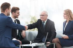 Partners concluding deal and shaking hands in the presence of team members Royalty Free Stock Photo