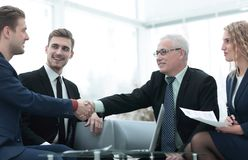 Partners concluding deal and shaking hands in the presence of team members Stock Image