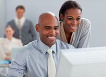Partners die bij een computer samenwerken stock foto's