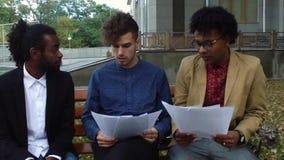 Partners die de documenten op de straat kijken stock footage