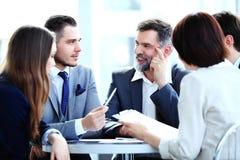 Partners die documenten en ideeën bespreken op vergadering royalty-vrije stock afbeelding