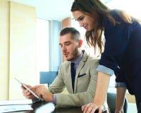 Partners die documenten en ideeën bespreken op vergadering Stock Afbeelding
