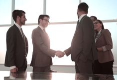 Partners die een bedrijfsbespreking in een zonnig bureau hebben stock afbeelding
