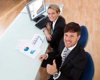 Partners die een bedrijfsgrafiek bespreken Stock Afbeelding