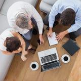 Partners die en een koffie samenwerken hebben Stock Foto's