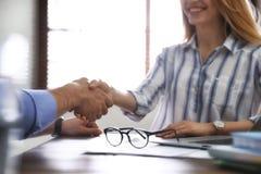Partners die handen schudden bij lijst na vergadering in bureau stock afbeelding