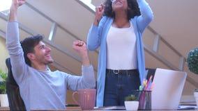 Partners die online succes vieren op kantoor stock footage