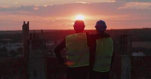 Partners för konstruktionsplats som två ser fantastisk stadssikt och solnedgång och rymmer som vänner arkivfilmer
