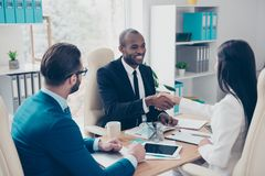 Partners making deal, shaking their hands, sitting in work place. Wearing elegant, classic suits, to sign a contract, three professional, confident, stylish Stock Images
