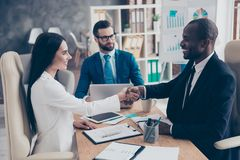 Partners making deal, shaking their hands, sitting in work place. Wearing elegant, classic suits, to sign a contract, three professional, confident, stylish Royalty Free Stock Images