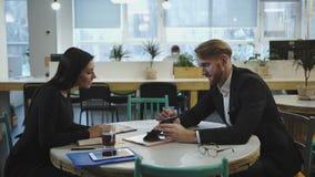 Partners op de vergadering De dame bespreekt strategie met een mens stock footage