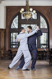 Partners Performing Argentine Tango In Restaurant. Full length of male partners performing Argentine tango in restaurant Stock Photos