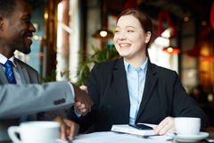 Partners Shaking Hands on Business deal. Portrait of two business people meeting in modern cafe: Young professional women shaking hands with  African-American Royalty Free Stock Images