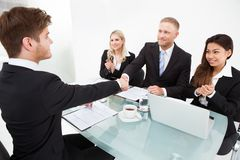 Partners shaking hands at desk Royalty Free Stock Image