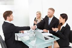 Partners shaking hands at desk Stock Image