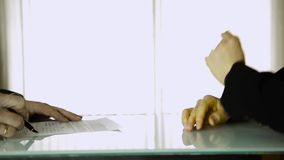 Partners signing contract. Close-up female client hands and male businessman hands with pan.  stock video footage
