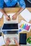 Partners som arbetar på skrivbordet genom att använda bärbara datorn Arkivfoto