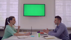 Partners talking in start up. Happy smiling partners in startup company. Coworkers talking sitting at the desk in creative office. Adult employees wearing casual stock video footage
