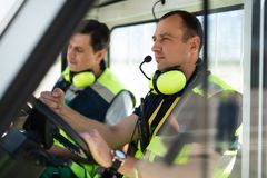 Airport male worker sitting in the care with colleague on blurred background royalty free stock photography